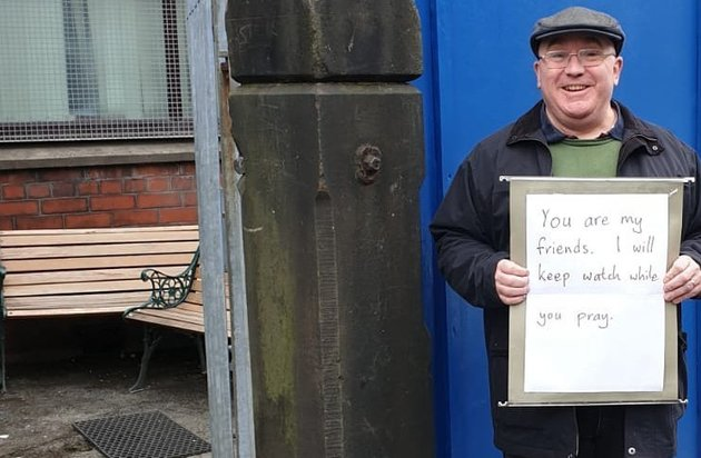man holds sign you are my friends. i will watch while you pray - manchester man outside of mosque